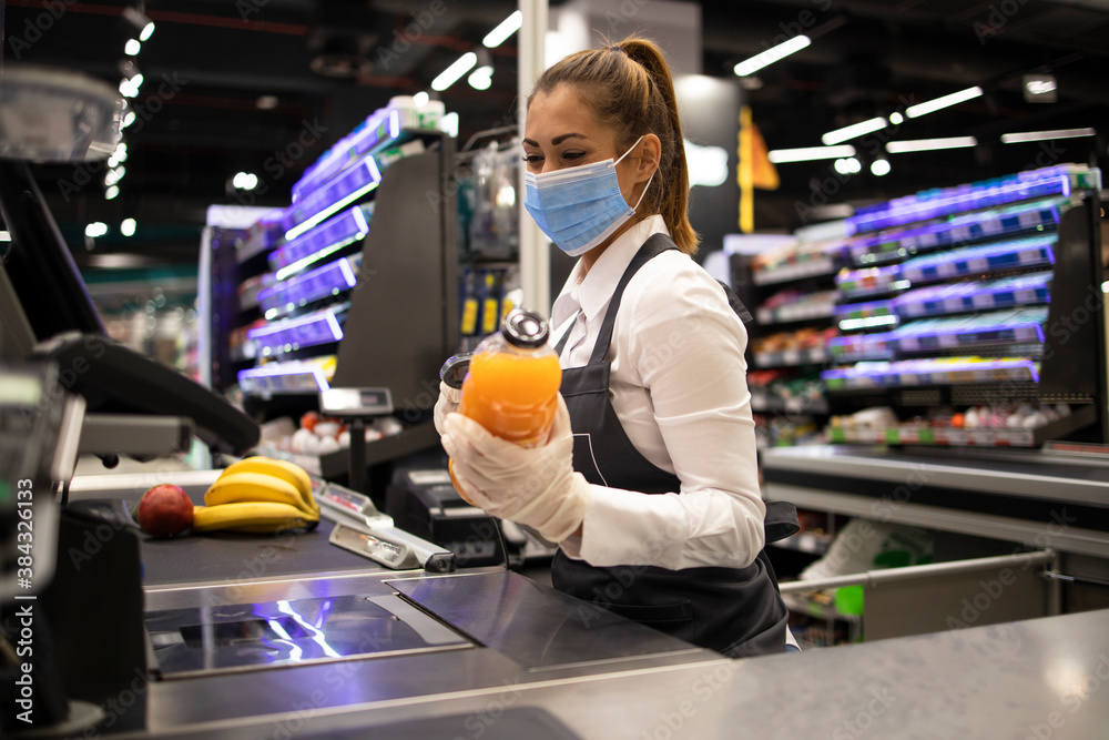 Fototapeta Working during covid-19 pandemic. Cashier at supermarket wearing mask and gloves fully protected against corona virus.