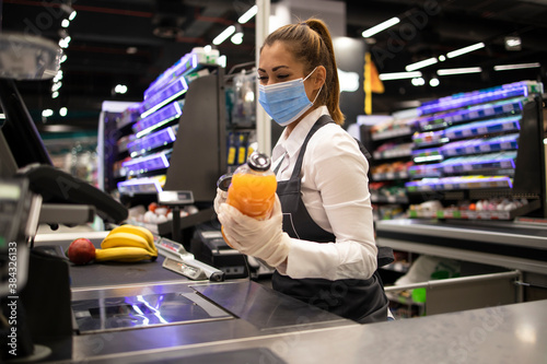 Obraz Working during covid-19 pandemic. Cashier at supermarket wearing mask and gloves fully protected against corona virus. - fototapety do salonu