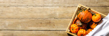 Ripe Pumpkins In A Wooden Box On A Wooden Background. Harvest Concept, Autumn, Halloween Eve. Banner. Flat Lay, Top View