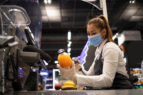 Working during covid-19 pandemic. Cashier in grocery store wearing mask and gloves fully protected against corona virus.