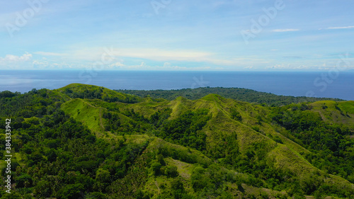 Hills and mountains covered with green grass against a background of blue sky and clouds. Bohol, Philippines. Summer landscape. #384333942