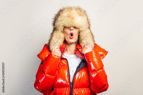 Fotografie, Obraz surprised beautiful young girl in a red jacket and fur hat, hat closes her eyes on a light background