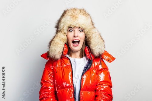 Fototapeta young girl in a red jacket and a fur hat, screaming with open eyes on a light background