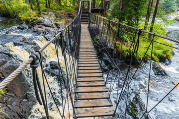 Panel Szklany Wodospad Suspension bridge and the cascades of Akhvenkoski waterfalls on the Tokhmayoki River, a popular tourist attraction situated near the settlement Ruskeala in Karelia, Russia
