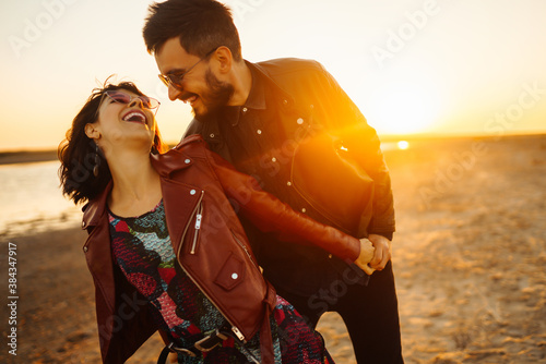 Fototapeta Romantic couple enjoying beautiful sunset walk on the beach travel autumn vacation. Enjoying time together. The concept of youth, love and lifestyle. obraz