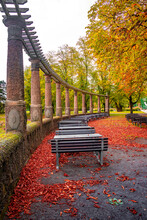 Lonely Empty Benches Under Old Chestnut Trees And Old Columns With Fallen Red And Orange Leaves In The City Park In Autumn Colors, Magdeburg, Germany.