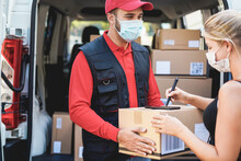 Young Woman Receiving A Cardboard Package From Delivery Man Wearing Face Mask - Courier At Work During Coronavirus Outbreak - Focus On Right Girl's Hand
