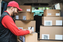 Happy Courier Man With Signing On Tablet For Delivery Boxes - Technology, Tracking And Shipment Service Concept - Focus On Face