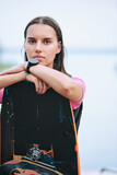 Young serious brunette female surfer with wristwatch standing behind surfboard