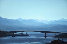 Silhouette Of The Arch Bridge Over The Lake Against The Backdrop Of Beautiful Mountains. Skye Bridge. Scotland, United Kingdom