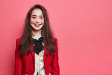 Halloween Portrait Of Cheerful Woman With Professional Makeup Being In Good Mood Wears Costume And Going On Masquerade Party Poses Against Rosy Background With Blank Space For Your Information