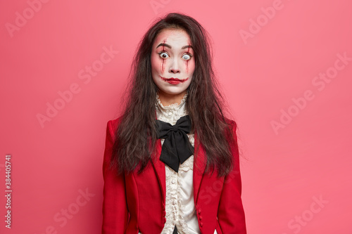 Fototapeta Shocked brunette woman with scars on face prepares for halloween festival stares bugged eyes tries to be dangerous isolated on pink background. Scarying horrible female vampire or zombie indoor obraz