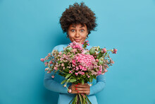Pretty Joyful Afro American Woman With Curly Hair Holds Big Bouquet Of Flowers Receives Nice Present On Anniversary Or 8 March Holiday Poses Indoor Against Blue Background. Celebration Concept