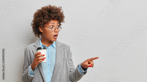 Fototapeta Stunned female lawyer with greatly surprised expression points away on copy space drinks takeaway coffee and wears formal clothes indicates something isolated on grey background. Check this out obraz