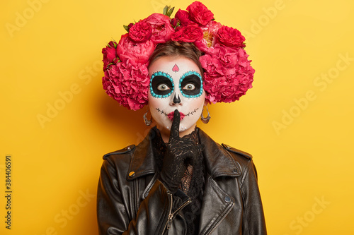 Mysterious mexican woman wears sugar creative makeup and makes silence gesture prepares for day of death in Mexico or religion ritual isolated on yellow wall. Dead katrina bride with floral garland