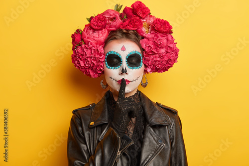 Portrait of mysterious spooky woman with creative sugar skull makeup celebrates Mexico day of death wears peonies wreath and leather jacket makes silence gesture isolated on yellow background.