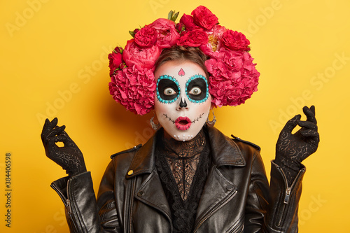 Fotomural Scared emotional woman wears scary makeup and floral headwear stares bugged eyes keeps mouth opened isolated over vivid yellow background