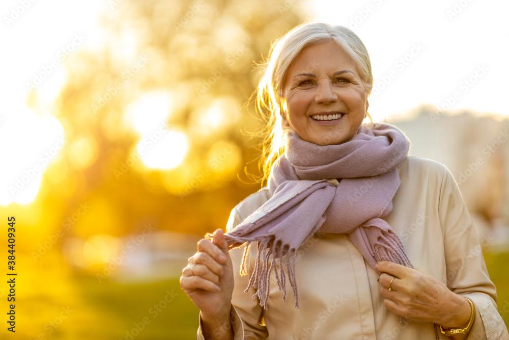 Fototapeta Senior woman enjoying autumn colors at sunset  - obraz na płótnie