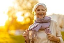 Senior Woman Enjoying Autumn Colors At Sunset
