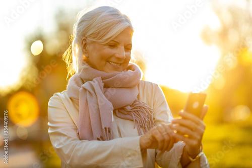 Fototapeta Senior woman using mobile phone outdoors at sunset  obraz na płótnie