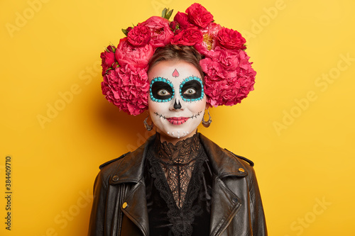 Obraz na plátně Cheerful female with artistic halloween makeup wears traditional attire for mexican day of death to honor dead relatives has spooky image poses against yellow background