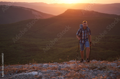 Hike mountain man hiking travel with backpack and trekking poles walking at adventure and sunset Wallpaper Mural