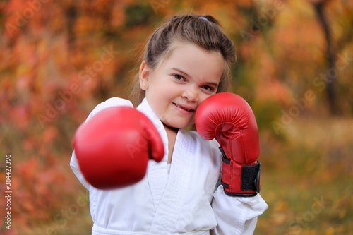 Fototapeta Little girl training the boxing punch