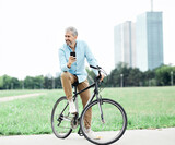 senior man smartphone bicycle cycling cell mobile phone outdoor city park businessman business casual