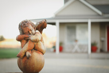 Close Up Image Of Stone Cherub Statue In Front Garden Of Newly Built House