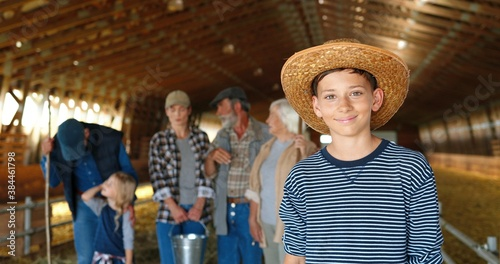 Fototapeta Portrait of Caucasian small teen boy in hat standing in shed and smiling to camera