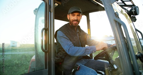 Photo Portrait of young Caucasian male farmer in cap sitting in tractor with open door and smiling to camera