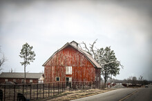 Old Vintage Red Wood Barn In Country With Metal Corral And Truck Approching On Two Lane Blacktop Hgihway