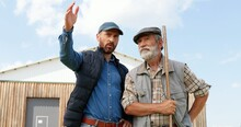 Caucasian Young Man Standing Outdoor With Old Retired Father In Farm And Talking, Asking For Advice. Males Farmers Speaking And Discussing Farming Work. Countryside. Son And Senior Father.