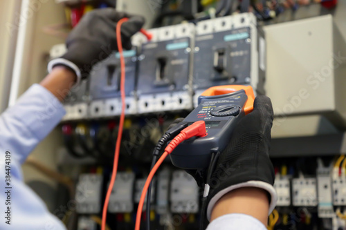 Electrical engineer using measuring equipment to checking electric current voltage at circuit breaker and cable wiring system for maintenance in main power distribution board Fotobehang