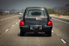 A Black Hearse Driving Down A Freeway