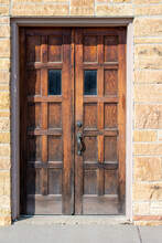 Antique Western Style Wooden Double Doors On An Old Limestone Block Wall Building In Bright Sunlight With Copy Space