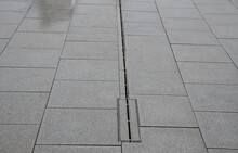 Large-format Paving Made Of Gray Granite. The Water Is Drained In The Rain Through A Slotted Stainless Steel Channel Which Is Sunk Under The Surface Of The Tile.