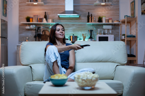 Caucasian woman sitting on couch and watching tv relaxing after work Canvas Print