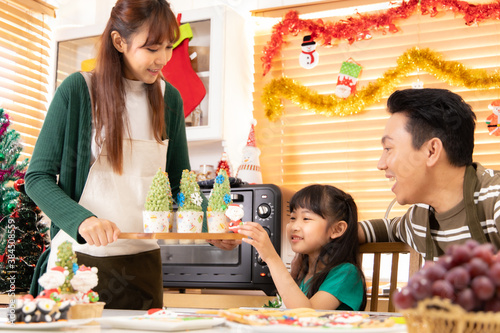 Thanksgiving or christmas Celebration Asian  Family Dinner Concept.family having holiday dinner.Happy family cooking for party. father mother and daughter, having dinner at home.