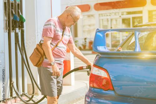 Fotografie, Obraz old senior man refill his car with gasoline on the fuel station, tourist traveli