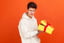 Dissatisfied Frustrated Teenager In Casual Hoodie Holding Open Gift Box, Upset With Bad Present, Unjustified Expectations. Indoor Studio Shot Isolated On Orange Background