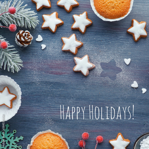 Christmas background with star cookies, tasty lemon muffins, winter decor. Text Happy Holidays. © tilialucida