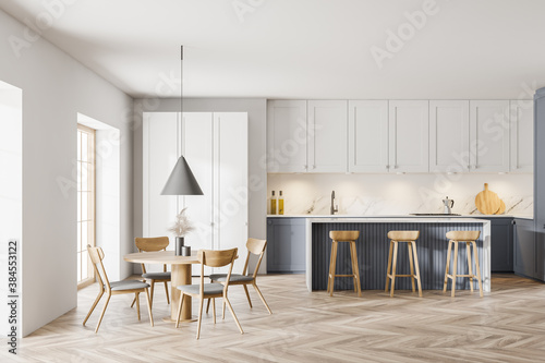 Modern white and gray kitchen with dining table and bar - 384553122