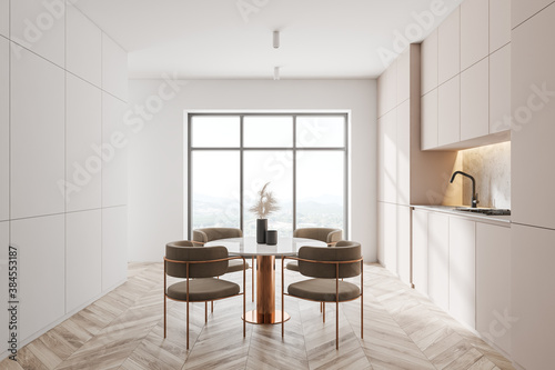 Modern white kitchen with dining table, side view