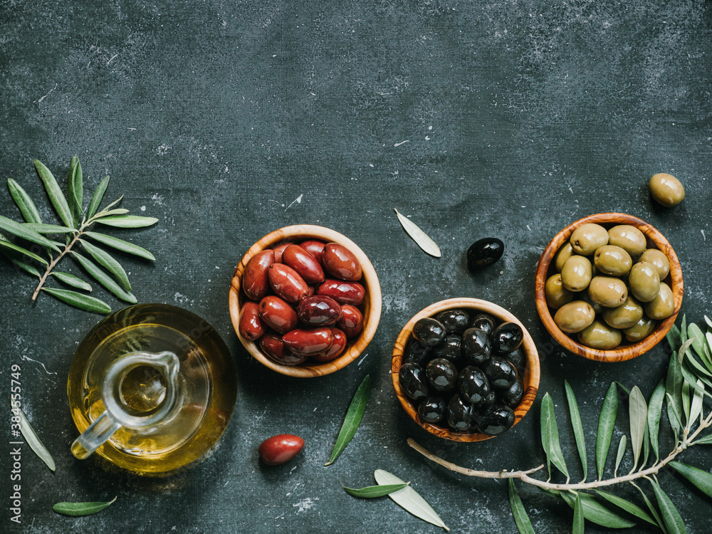 Fototapeta Set of green, black and red or pink olives and olive oil on dark background. Different types of olives in olive wooden bowls and olive oil over dark canvas background. Copy space. Top view or flat lay