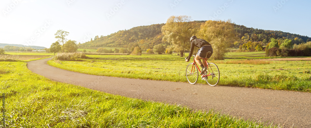 Fototapeta Panorama shot of cyclist on a racing bike in scenic rural autumn landscape during beautiful afternoon light
