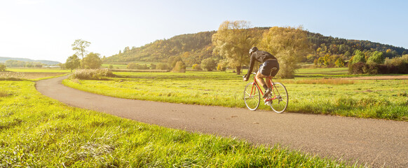 Panorama shot of cyclist on a racing bike in scenic rural autumn landscape during beautiful afternoon light