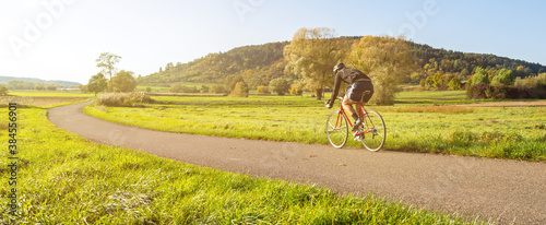 Fototapeta Panorama shot of cyclist on a racing bike in scenic rural autumn landscape during beautiful afternoon light obraz