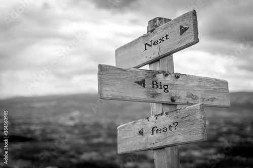 Fotografering next big feat text quote on wooden signpost outdoors in black and white