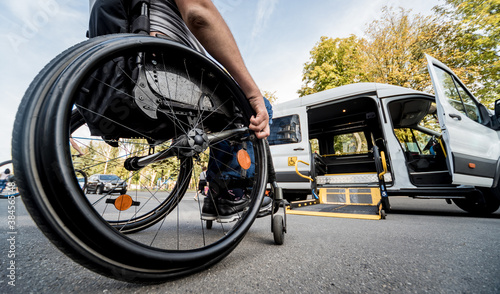 Obraz na plátně A man in a wheelchair moves to the lift of a specialized vehicle